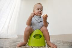 Baby sitting on potty and eating vegetables. At home interior stock photography