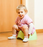 Baby sitting on potty in home. Toddler sitting on potty in home interior stock images