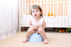 Baby sitting on potty in home. Baby boy sitting on potty in home Stock Image