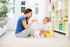 Baby sitting on potty and playing with smiling beautiful mother Stock Image