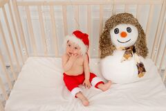 Baby sitting in a Santa hat with a snowman in the nursery in the crib, happy new year 2021, space for text