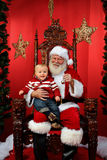 Baby Sitting on Santa's Lap. Baby boy sitting on Santa's lap at Christmas time Stock Image