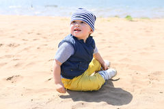 Baby sitting on shore of the lake Royalty Free Stock Images