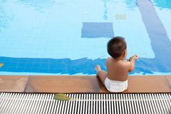 Baby sitting side of the pool Royalty Free Stock Image
