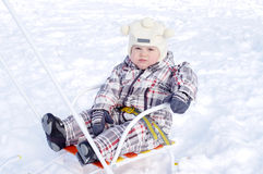 Baby sitting on sledge Royalty Free Stock Images