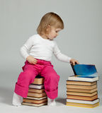 Baby sitting on stacked books Stock Photo