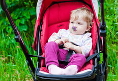 Baby sitting in stroller with fun look on summer. Green background royalty free stock photos