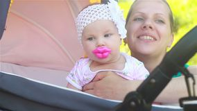 Baby sitting in a stroller with a funny nipple in the form of huge lips stock video