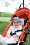 Baby in sitting stroller on nature. Smiling baby in sitting stroller on nature Stock Image