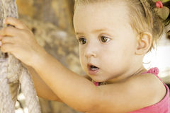 Baby sitting on swing and looking off into the distance.  Royalty Free Stock Photos