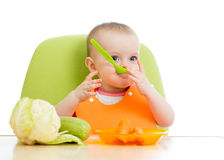 Baby sitting at table with healthy food Stock Photo
