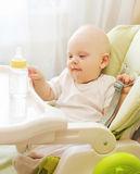 Baby sitting at table home with plastic bottle Royalty Free Stock Photos
