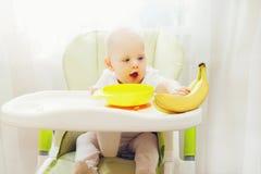 Baby sitting at table home and takes fruits bananas royalty free stock photos