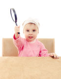 Baby sitting at a table with magnifying glass Stock Photography