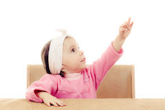 Baby sitting at the table. Points a finger at the top Stock Photos