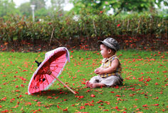Baby sitting with umbella. Baby sitting with umbrella  alone without family Royalty Free Stock Photography