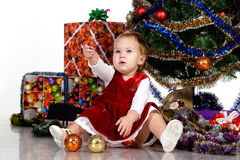 Baby sitting under a Christmas tree Royalty Free Stock Photography
