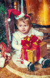 Baby sitting under christmas tree in room Stock Photography
