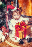Baby sitting under christmas tree in room Royalty Free Stock Images
