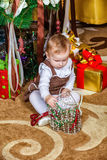 Baby sitting under christmas tree in room Royalty Free Stock Image
