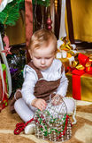 Baby sitting under christmas tree in room Stock Images