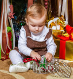 Baby sitting under christmas tree in room Stock Photos