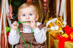 Baby sitting under christmas tree in room Royalty Free Stock Photos