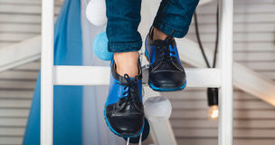 Baby sitting on a white wheel wearing blue jeans and black shoes Royalty Free Stock Photography