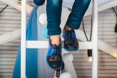 Baby sitting on a white wheel wearing blue jeans and black shoes Stock Photography