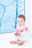 Baby sitting at window watching snow covered trees Stock Photo