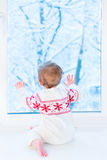 Baby sitting at window watching snow covered trees Royalty Free Stock Images