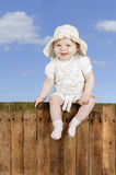 Baby sitting on a wooden fence Stock Photography