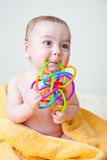 Baby Sitting on Yellow Towel Gnawing Toy. Caucasian baby boy after bath wrapped in soft fluffy yellow towel sitting holding and gnawing a multicolored toy Stock Photos