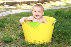 Baby sitting in yellow tub Stock Photography