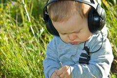 Baby sitzt auf einer Wiese mit Kopfhörern Stockbilder