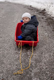 Baby in sled. Baby sitting in a sled on an almost snow free road, wondering where the winter went Stock Images