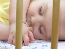 Baby sleep. In bed with hand Stock Images
