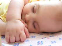 Baby sleep. In bed with hand Royalty Free Stock Photography