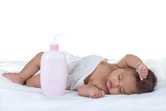 Baby sleep on a bed. On white background with baby product in front of she Stock Image