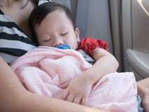Baby sleep in car with dummy in mouth. Royalty Free Stock Photos