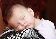 Baby sleep on hands of mother Stock Image