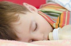 Baby sleep. Little baby boy sleeping with milk bottle Royalty Free Stock Photo