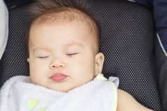 Baby sleep outdoor in a baby car Royalty Free Stock Photo