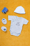 Baby sleep suit with cap, shoes and toy Stock Photos