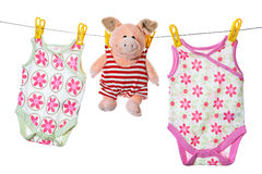 Baby sleepers and pig on the clothesline. Studio isolated on white stock photos