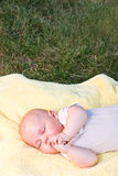 Baby sleeping. In a yellow towel in nature Royalty Free Stock Images