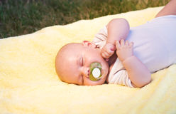Baby sleeping. In a yellow towel in nature with nipple Royalty Free Stock Photography