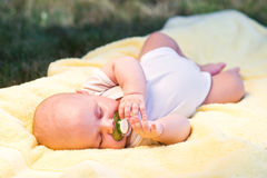 Baby sleeping. In a yellow towel in nature with nipple Stock Image