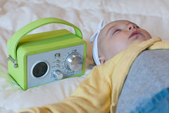 Baby sleeping with alarm clock. Baby with onesie sleeping with alarm clock Royalty Free Stock Photos