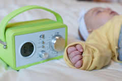 Baby sleeping with alarm clock. Baby with onesie sleeping with alarm clock Stock Photo
